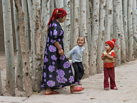 ཤིན་ཅང་གི་ཁཱ་ཤི་སྒར་(Kashgar)་ནང་བུད་མེད་ཞིག་གིས་བྱིས་པ་ཁྲིད་ནས་བསྐྱོད་བཞིན་པ། ༼ཟླ་ཚེས་མི་གསལ